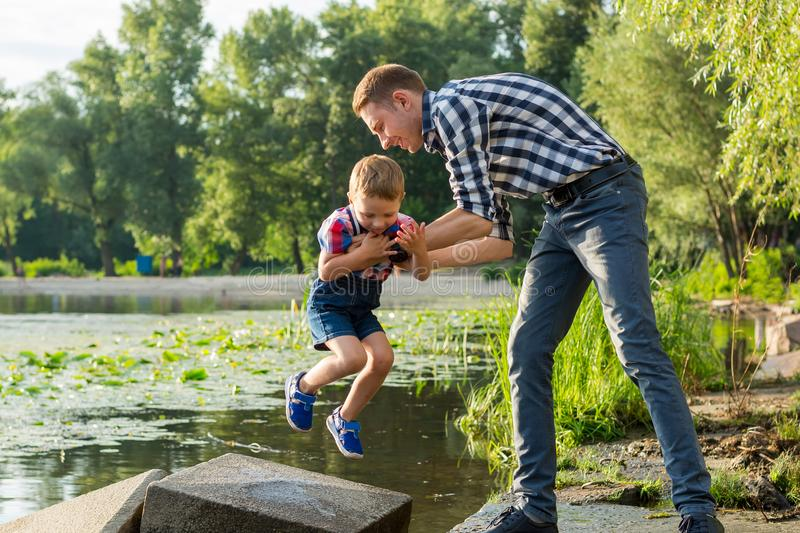 Dad lifts his little son in his arms at the river background royalty free stock photos