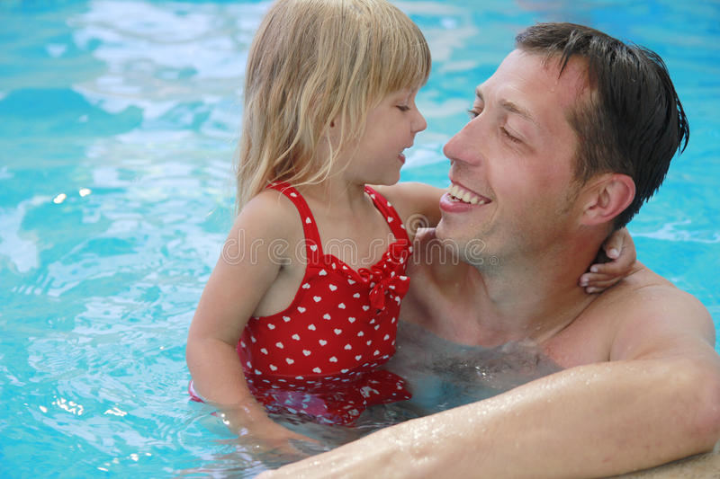 Dad and little daughter in the water pool
