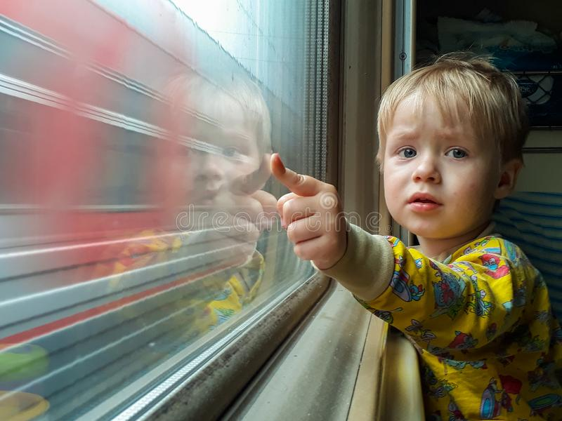 Dad, look - the train! A little blond-haired boy of three years rides on a train, eats candy and looks out the window royalty free stock image