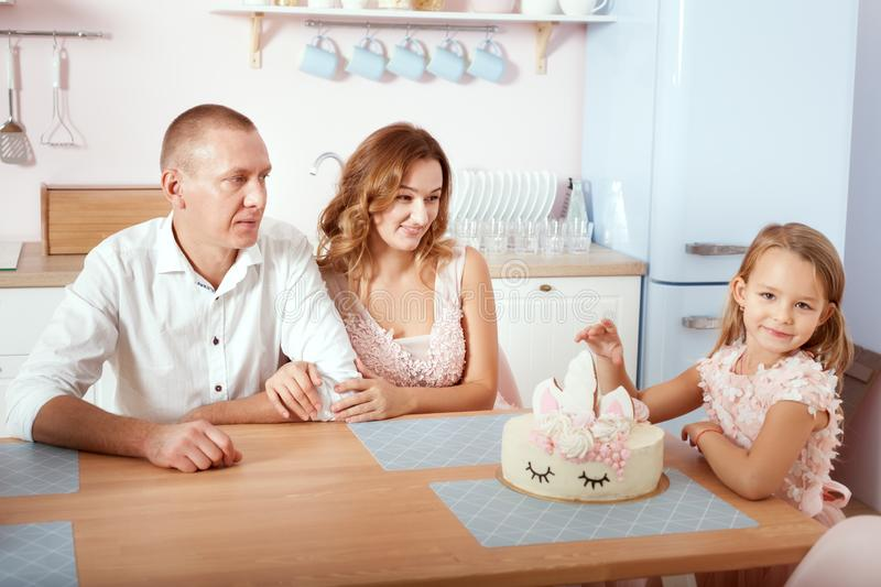 Dad, mom and daughter are sitting in the kitchen at the table stock photography