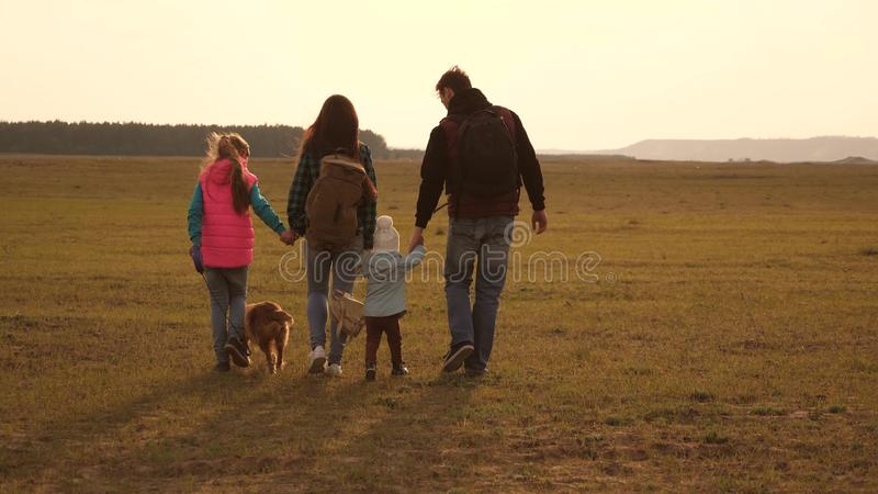Dad, mom, daughters and pets, tourists. teamwork of a close-knit family. the family travels with the dog across the. Dad, mom, daughters and pets, tourists stock photo