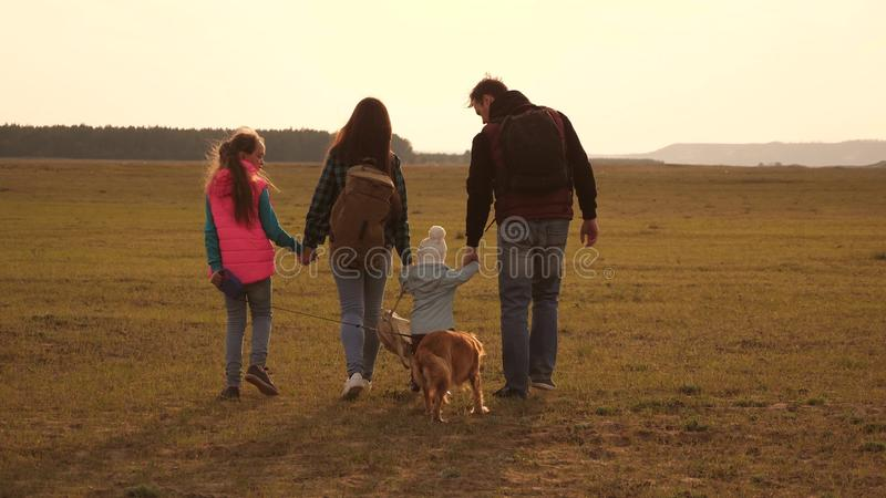 Dad, mom, daughters and pets, tourists. teamwork of a close-knit family. the family travels with the dog across the. Dad, mom, daughters and pets, tourists royalty free stock photos
