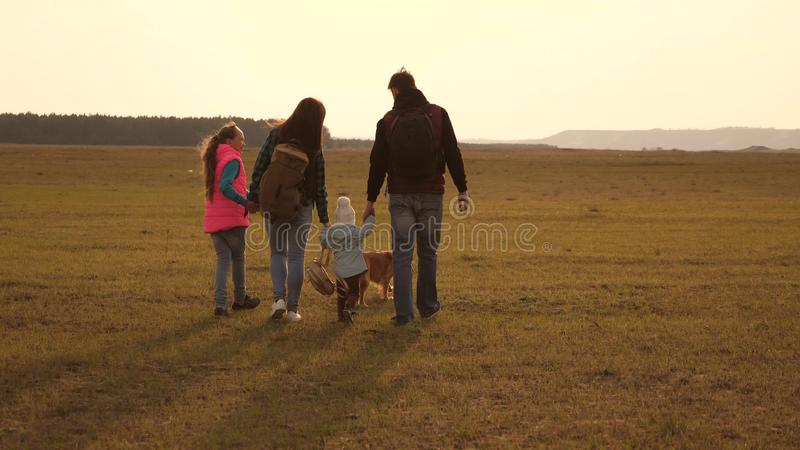 Dad, mom, daughters and pets, tourists. teamwork of a close-knit family. the family travels with the dog across the. Dad, mom, daughters and pets, tourists royalty free stock images