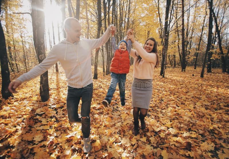 Dad and mom raised their son upside and walking along the park path. Happy family resting in the park in sunny day. royalty free stock photography