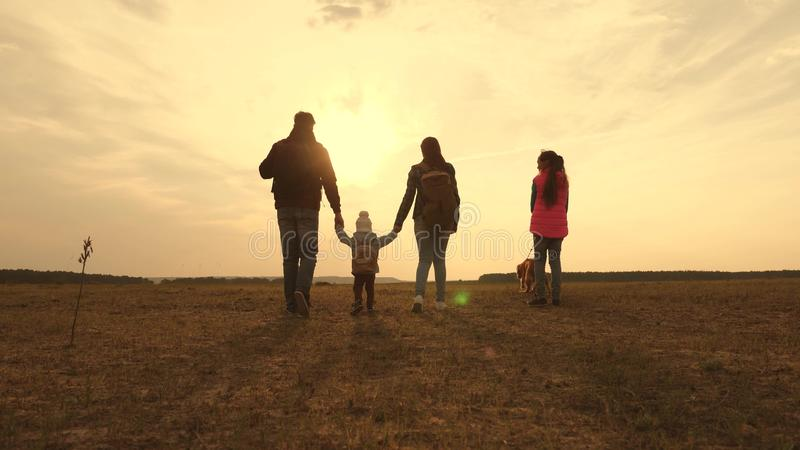 Dad, Mom, a small child and daughters and pets tourists. teamwork of a close-knit family. family travels with the dog on. Dad, Mom, small child and daughters and stock image