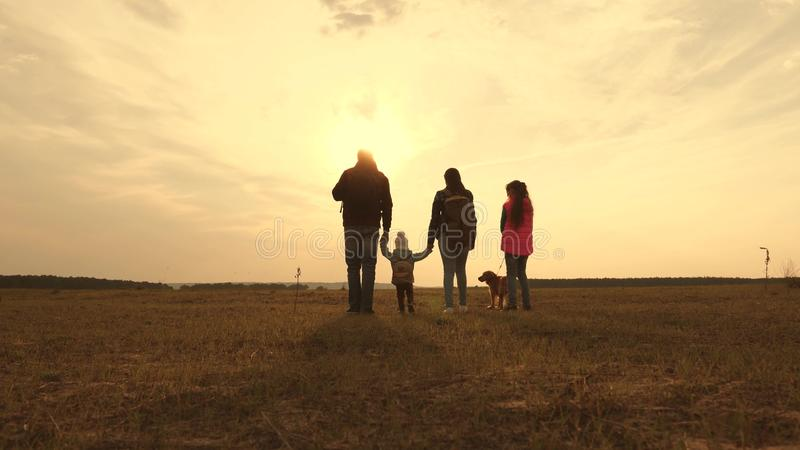 Dad, Mom, a small child and daughters and pets tourists. teamwork of a close-knit family. family travels with the dog on royalty free stock image
