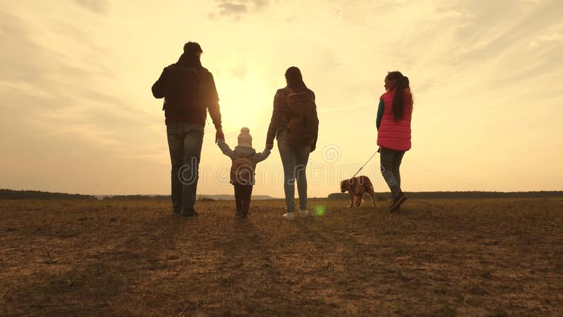 Dad, Mom, a small child and daughters and pets tourists. teamwork of a close-knit family. family travels with the dog on royalty free stock images