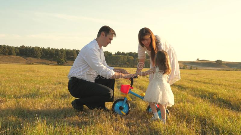 Dad and Mom teach daughter to ride a bike. Mother and father play with small child on lawn. kid learns to ride bicycle royalty free stock photography
