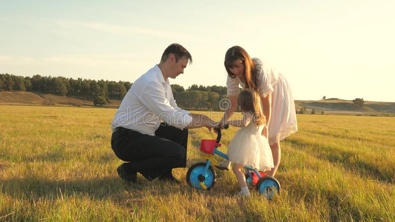 Dad and Mom teach daughter to ride a bike. Mother and father play with small child on lawn. kid learns to ride bicycle royalty free stock photo