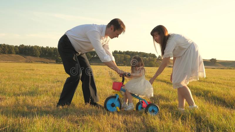 Dad and Mom teach daughter to ride a bike. Mother and father play with small child on lawn. kid learns to ride bicycle royalty free stock images