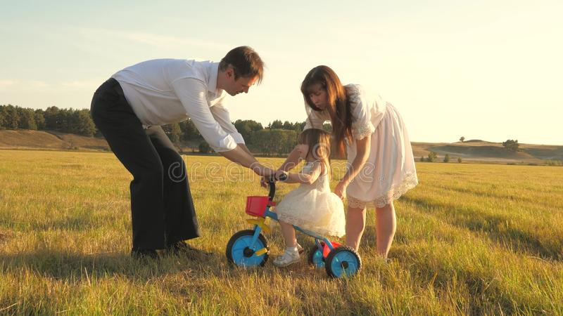 Dad and Mom teach daughter to ride a bike. Mother and father play with small child on lawn. kid learns to ride bicycle royalty free stock image