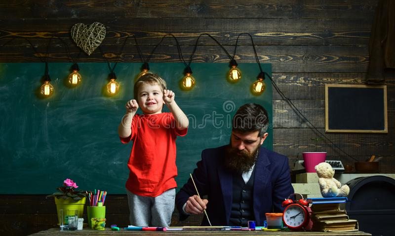 Dad painting while kid is playing. Little boy showing his fists standing next to his busy daddy. Concentrated father and royalty free stock photos