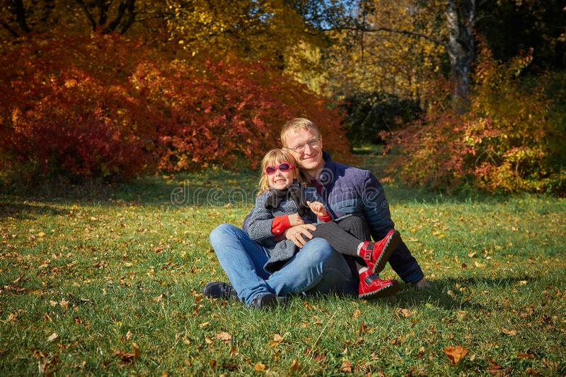 Dad plays with his daughter. In the autumn park royalty free stock images