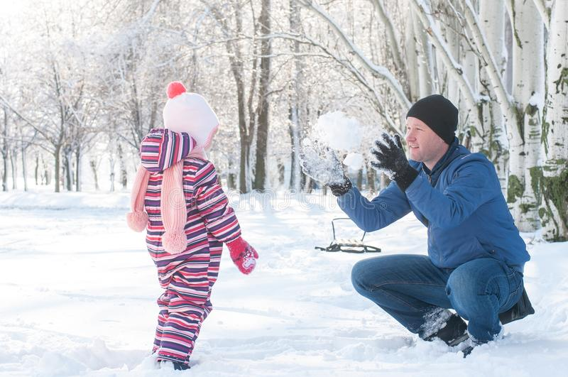 Dad plays with his daughter in the winter outside stock photo