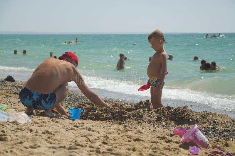 Dad plays with his son in the sand. stock image
