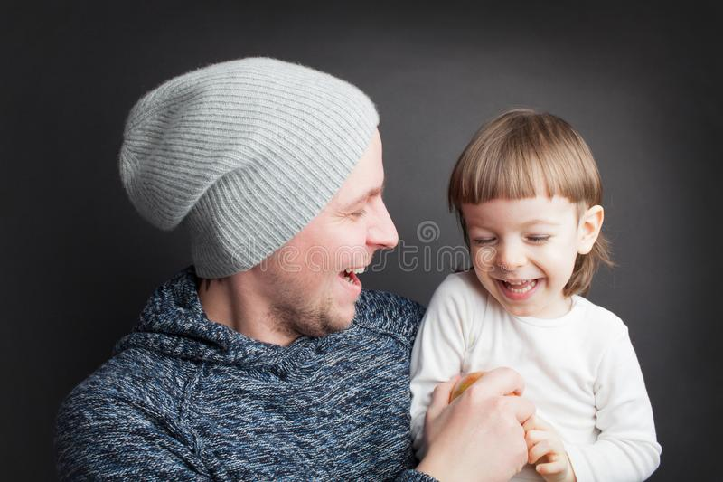 Dad plays with a lovely little son, sitting on his hands on a black background in the Studio. It amuses it with Apple and they bot royalty free stock photo
