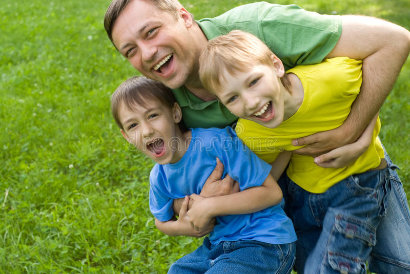 Dad plays with young children royalty free stock photos