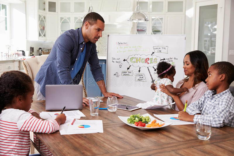 Dad presenting domestic meeting to his family in the kitchen royalty free stock photo