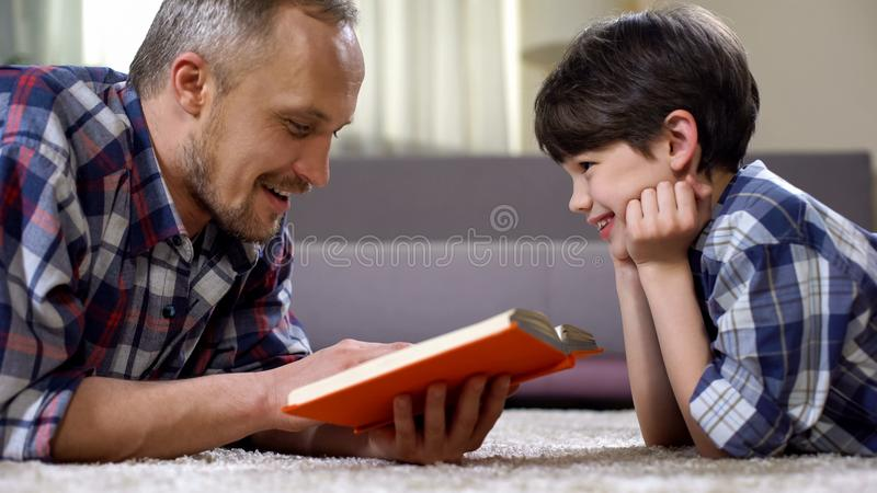 Dad reading son exciting fantasy book, imagination and creativity, leisure time royalty free stock image