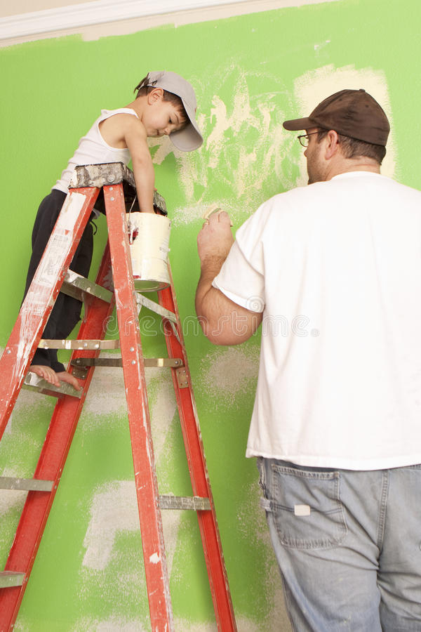 Dad's Helper. Young boy standing on a ladder helping his dad paint stock photography