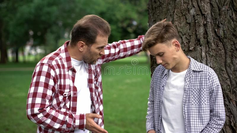 Dad scolding his son for bad behavior, education process, fathers and children stock images