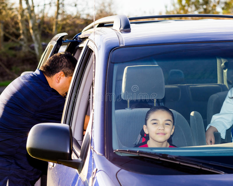 Dad Secures Son In Car Seat As Sisters Wait Patiently stock image