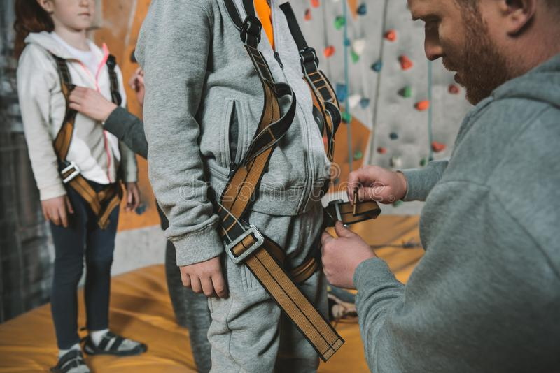 Cropped shot of dad securing his little son in a climbing harness. In gym stock photo