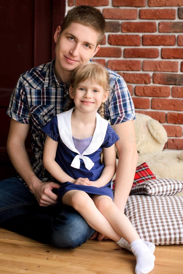 Dad sits with her daughter. In her arms, against a background of a brick wall royalty free stock photo