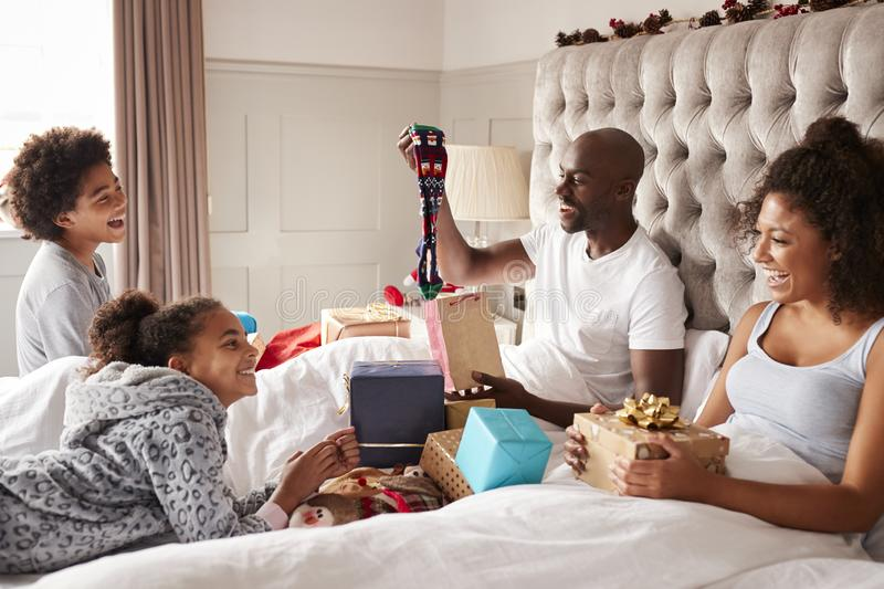 Dad sitting up in bed opening a gift on Christmas morning watched by his family, close up royalty free stock photography