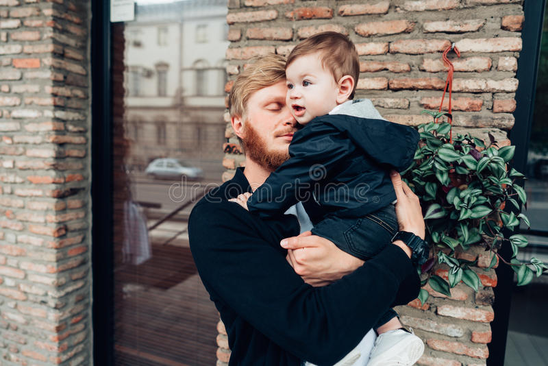Dad with a small son in his arms. Against the wall on the street stock photography