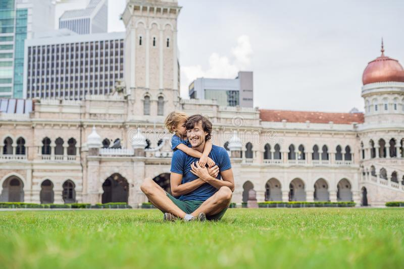 Dad and son on background of Merdeka square and Sultan Abdul Samad Building. Traveling with children concept.  royalty free stock images