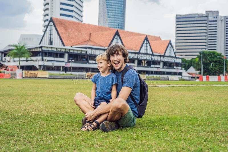 Dad and son on background of Merdeka square and Sultan Abdul Samad Building. Traveling with children concept stock image
