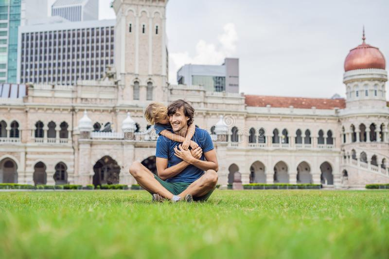 Dad and son on background of Merdeka square and Sultan Abdul Samad Building. Traveling with children concept stock photos