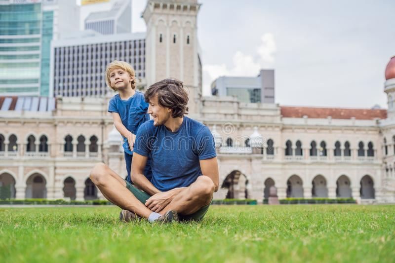 Dad and son on background of Merdeka square and Sultan Abdul Samad Building. Traveling with children concept royalty free stock image