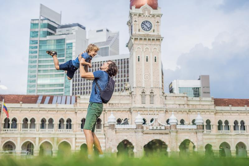 Dad and son on background of Merdeka square and Sultan Abdul Samad Building. Traveling with children concept royalty free stock photo