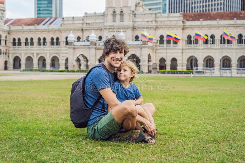 Dad and son on background of Merdeka square and Sultan Abdul Samad Building. Traveling with children concept.  royalty free stock photo