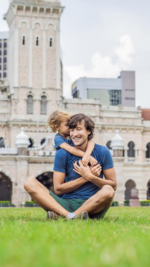 Dad and son on background of Merdeka square and Sultan Abdul Samad Building. Traveling with children concept VERTICAL. Dad and son on background of Merdeka royalty free stock images
