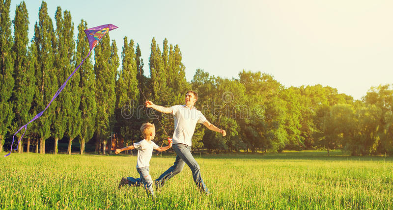 Dad and son child flying a kite in summer nature. Happy family in summer nature. Dad and son child flying a kite royalty free stock images