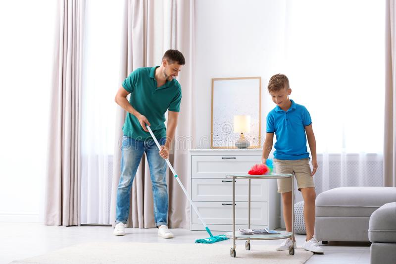 Dad and son cleaning room together royalty free stock image