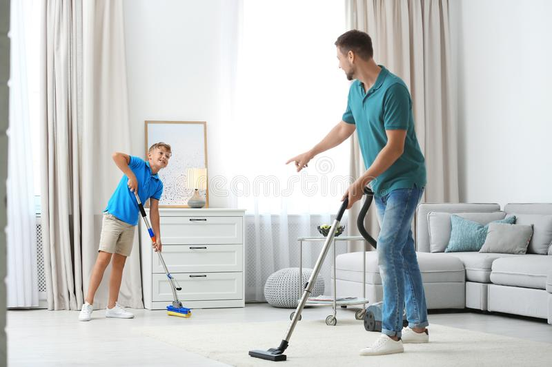 Dad and son cleaning room together stock image