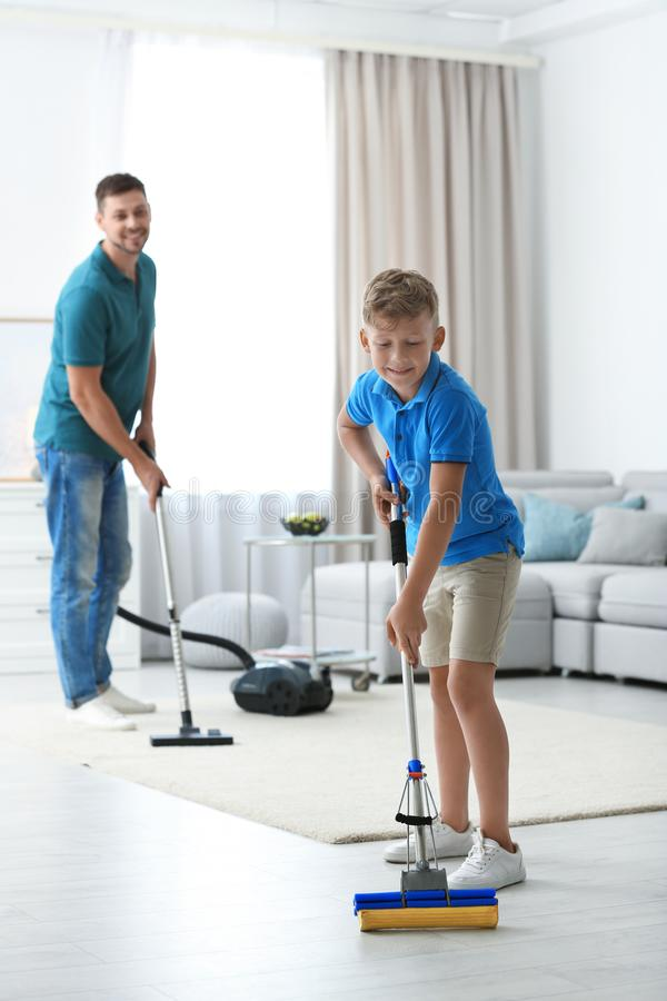 Dad and son cleaning room together stock photography