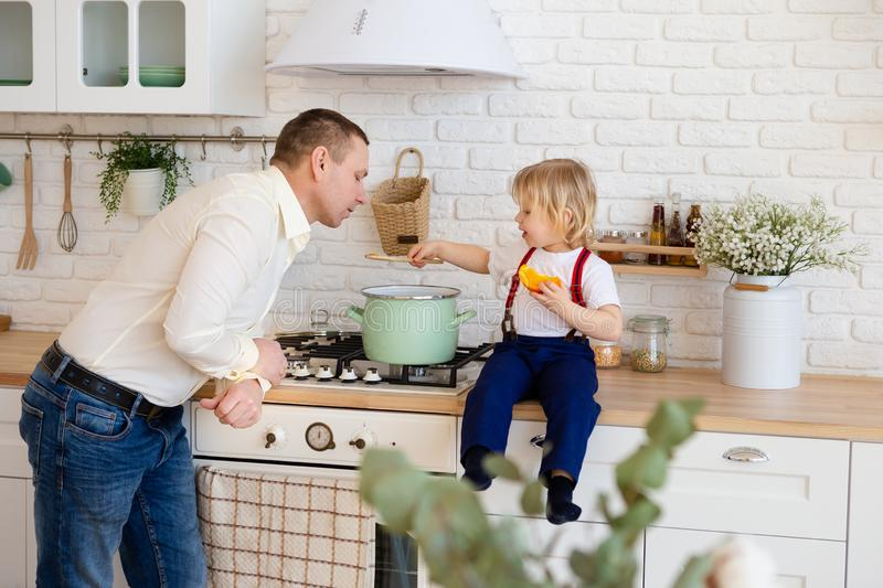 Dad and son cooking soup in pan stock image