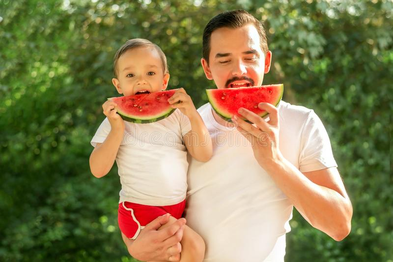 Dad and son eating and simultaneously biting slices of watermelon on picnic. Father is holding boy in arms royalty free stock photo