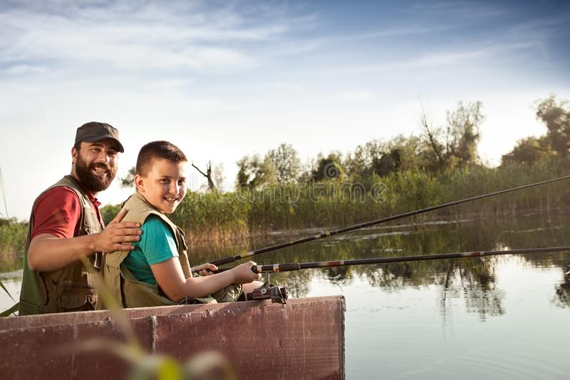 Dad and son fishing from boat on river. Dad and son fishing from wooden boat on river, happy family together in nature stock photo