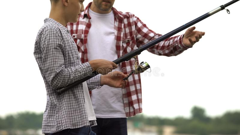 Dad and son fishing, escape from stressed city life, common interests, free time stock photography