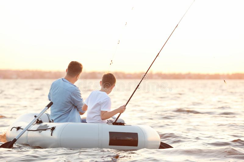 Dad and son fishing from inflatable boat. On river stock photography