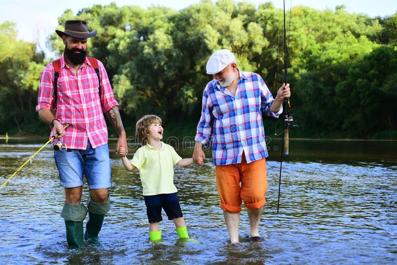 Dad and son fishing at lake. Young - adult concept. Men hobby. Grandfather, father and boy fishing together. royalty free stock photo