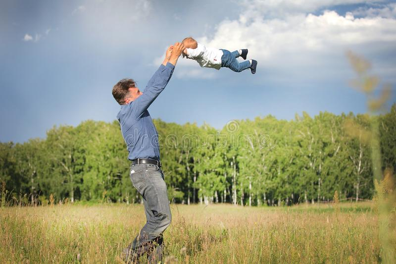 Dad and son frolic in the clearing. stock images