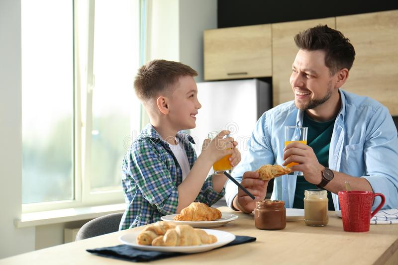 Dad and son having breakfast together in royalty free stock photography