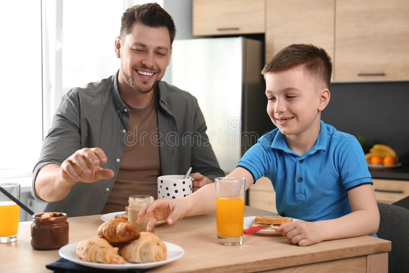 Dad and son having breakfast together in stock photography